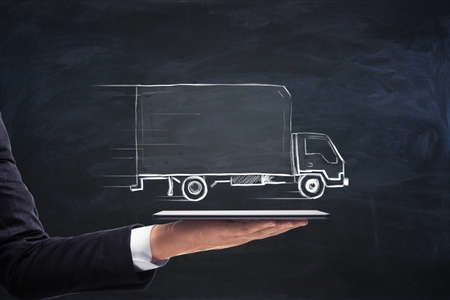 Businessman hand holding tablet with creative truck sketch. Transporation and logistics concept
