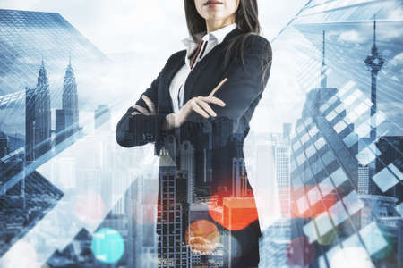 Businesswoman with folded arms standing on abstract city backdrop.