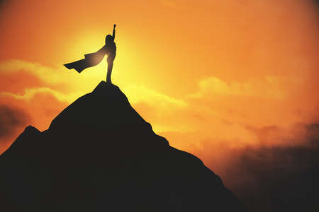 Woman in cape celebrating success on creative backlit mountain and sunset backdrop 免版税图像