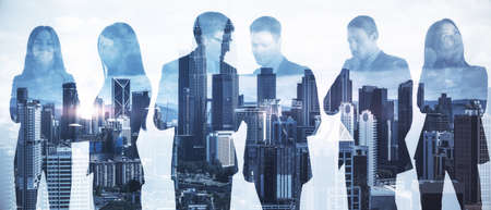 Businesspeople working together on abstract city backdrop.