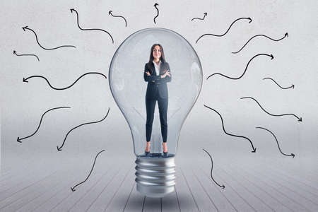 Lightbulb with businesswoman inside and arrows on concrete wall