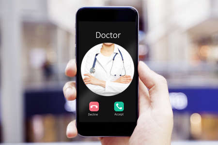 Close up of hand holding smartphone with incoming call from doctor 免版税图像