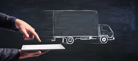 Transport logistics concept with handwritten white truck on abstract dark wallpaper and man hands with digital tablet