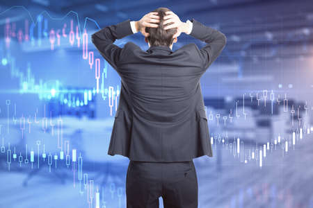 Back view of stressed young businessman in suit standing in modern office interior with forex chart.