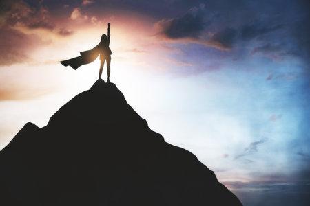 Winner and hero concept with superwoman in dark coat on top of the rock 免版税图像