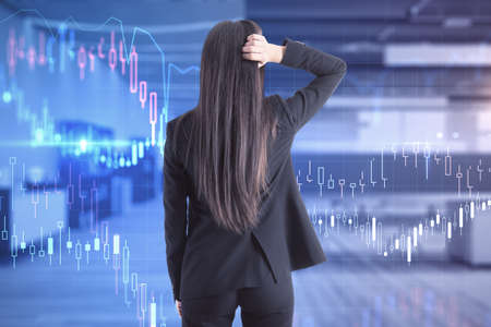 Back view of stressed young businesswoman in suit standing in modern office interior with forex chart.