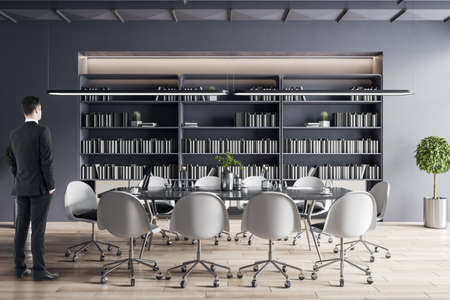 Businessman standing in modern meeting room interior with furniture, bookcase.