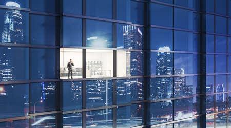 Overworking businessman still in the office at night 免版税图像