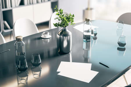 Blank white papers on dark glossy table with glasses and stylish vase in sunny room. 免版税图像