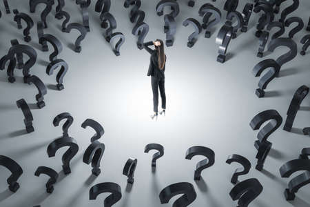 Making decision and finding solution concept with pensive businesswoman on light floor surrounded by black question marks 免版税图像
