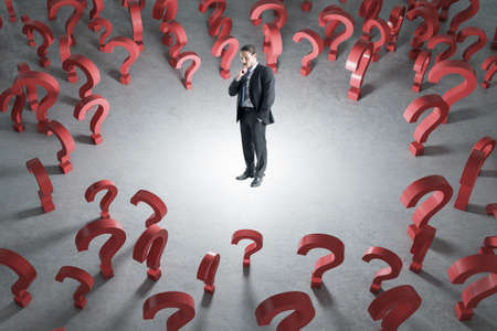 Thoughtful young businessman with red question marks on concrete background. Solution and quiz concept