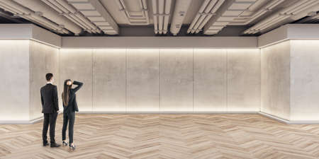 Businessmen and women looking at wall in modern exhibition space concrete interior with mockup place and wooden flooring. Mock up