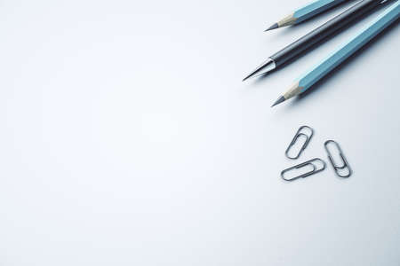 Close up of pencils and paper clips on white mockup desk backdrop, Stationery concept. 3D Rendering
