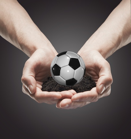 A handful soil with classic soccer ball in the hands photo