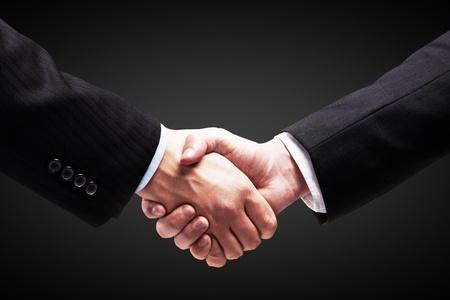 negotiating: Handshake - Hand holding on black background Stock Photo