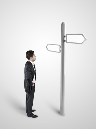 decide: Businessman standing at a crossroad. A signpost points at multiple directions