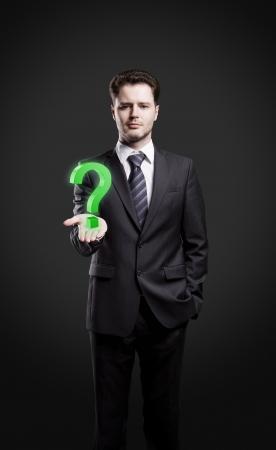 preguntando: Joven empresario con un signo de interrogación sobre su mano. Aislado en un fondo negro Foto de archivo