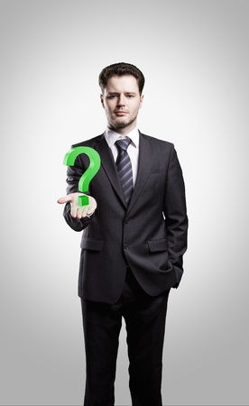 Young  businessman with a question mark on his hand. On a gray background Stock Photo - 10441628