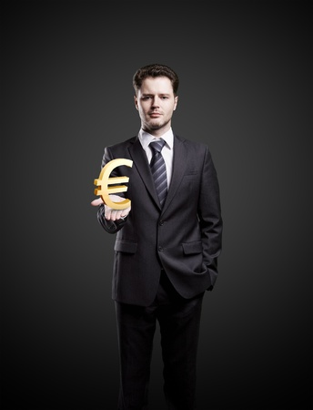 Young  businessman chooses a Gold Euro Sign.On a black background photo