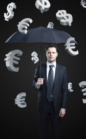 argent: Business man with umbrella under evro and dollar signs rain Stock Photo