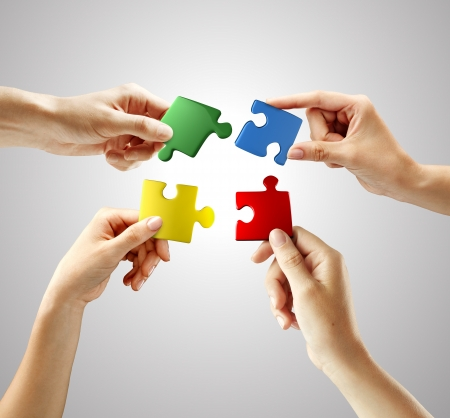 Hands and puzzle on gray background. Teamwork solving a puzzle photo