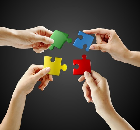 Handen en puzzel op zwarte achtergrond. Teamwerk oplossen van een puzzel Stockfoto