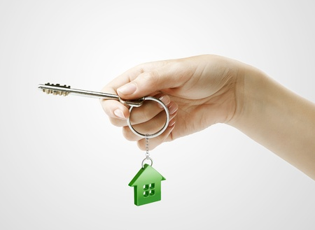 hand chain: Hand holding key with a keychain in the shape of the house. House key on the white background