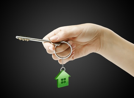 Hand holding key with a keychain in the shape of the house. House key on a black background photo