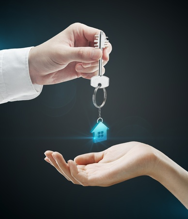 house key: Man is handing a house key to a woman.Key with a keychain in the shape of the house. On a black background