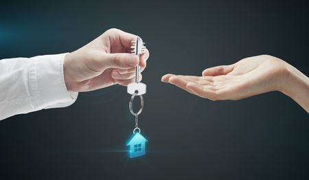 Man is handing a house key to a woman.Key with a keychain in the shape of the house. On a black background photo