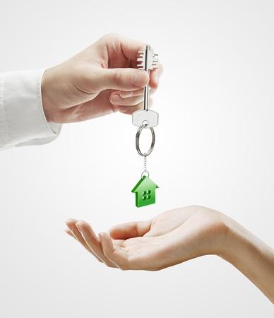 rental: Hombre entrega una llave de casa a una mujer.Clave con un llavero con la forma de la casa. Sobre un fondo gris Foto de archivo