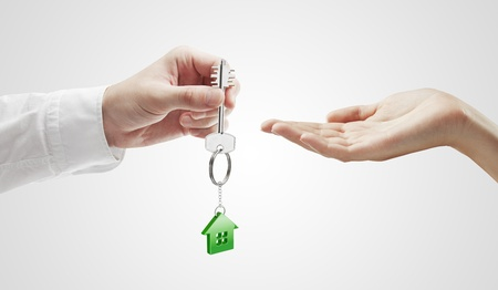 keychain: Man is handing a house key to a woman.Key with a keychain in the shape of the house. On a gray background