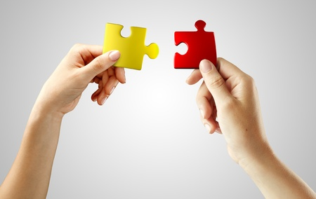 Hands with puzzle on gray background. Teamwork solving a puzzle photo
