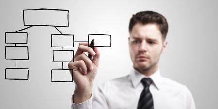 dataflow: Hombre de negocios el dise�o de un plan en una pantalla de vidrio con marcador negro.