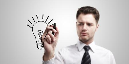 marcador: Hombre de negocios joven dibujar una bombilla en una pantalla de vidrio con marcador negro. Hombre con una idea. Sobre un fondo gris