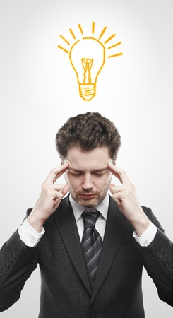 coming up with: Portrait of a young man with light bulb above his head. Man coming up with an idea. On a gray background