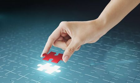 search solution: Hand embed missing puzzle piece into place. Business concept for completing the final puzzle place