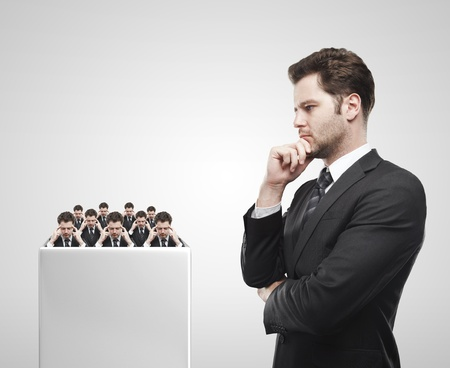 reasoning: Young  businessman look at the group of businessmen on a white pedestal. Thinking men representing a social network. Conceptual image of a open minded men.On a gray background