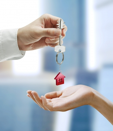 keychain: Man is handing a house key to a woman.Key with a keychain in the shape of the house.