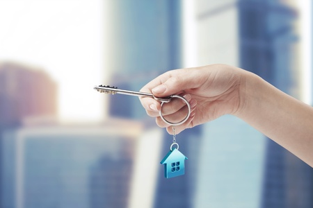 Hand holding key with a keychain in the shape of the house. House key Stock Photo - 11031203