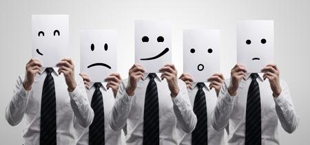 caras de emociones: Cinco hombres de negocios la celebración de una tarjeta con la cara emocional. Sobre un fondo gris