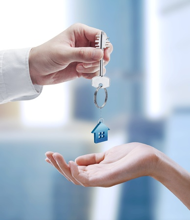 house sale: Man is handing a house key to a woman.Key with a keychain in the shape of the house.