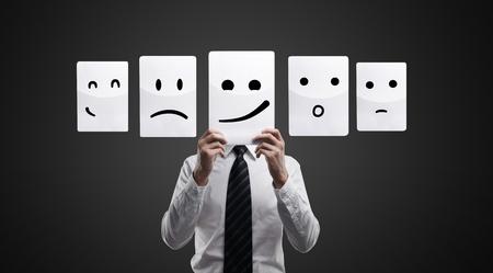 caras de emociones: Hombre de negocios la celebraci�n de una tarjeta con la cara sonriente. El hombre elige una caras emocionales. Sobre un fondo negro