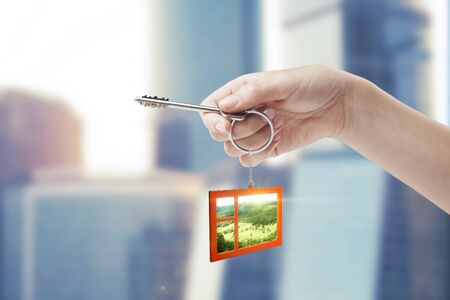Hand holding key with a keychain in the shape of the window. Beautiful view behind a window of a green field with a blue sky. House key  Stock Photo - 11031257
