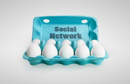 Group of happy eggs with smiling faces representing a social network. Ten white eggs in a carton box.  On a gray  background photo