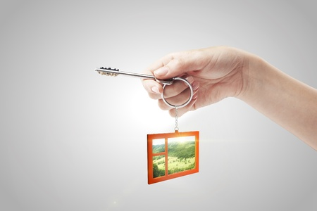 Hand holding key with a keychain in the shape of the window. Beautiful view behind a window of a green field with a blue sky. House key on a gray background Stock Photo - 11031244