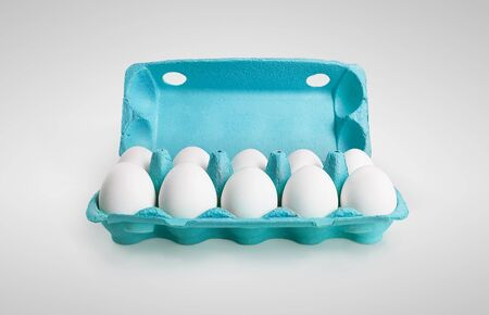 Ten white eggs in a carton box. On a gray background photo