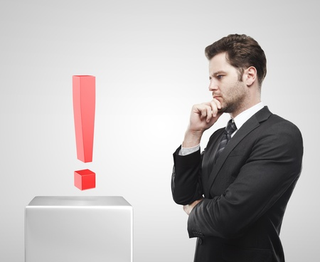 Young  businessman look at the red exclamation mark on a white pedestal. On a gray background  photo