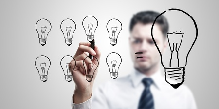 Young business man drawing many small light bulbs equal a big one. Stock Photo - 11094396
