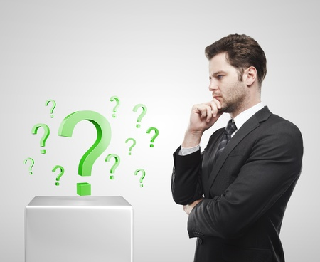 unanswered: Young  businessman look at the green question marks on a white pedestal. On a gray background  Stock Photo
